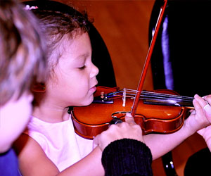 Photo of a child learning to play the violin by the Knight Foundation