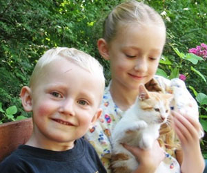 Young brother and sister with a cat